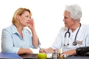 Frau mit Migräne bei einer älteren Ärztin