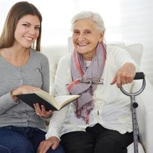 Frau beim Freiwilligendienst liest Senioren vor